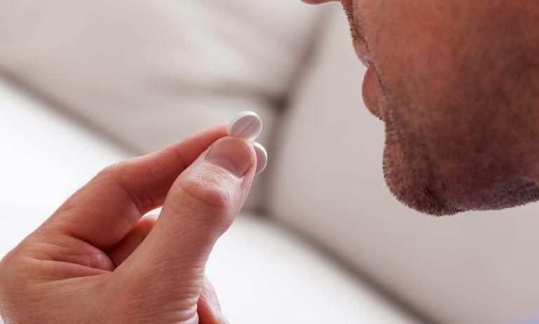 man eating a pill
